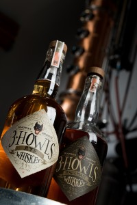Bottles of 3 Howls Whiskey sit in front of the stills at their distillery in Seattle, WA. Photography by Ari Shapiro - The Whisky Guy